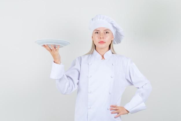 Köchin, die platte in der weißen uniform hält und ernst schaut