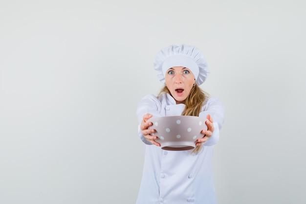 Köchin, die schüssel in weißer uniform zeigt und überrascht schaut