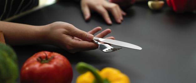 Köchin, die silberne gabel und tischmesser hält, während sie esstisch einstellt