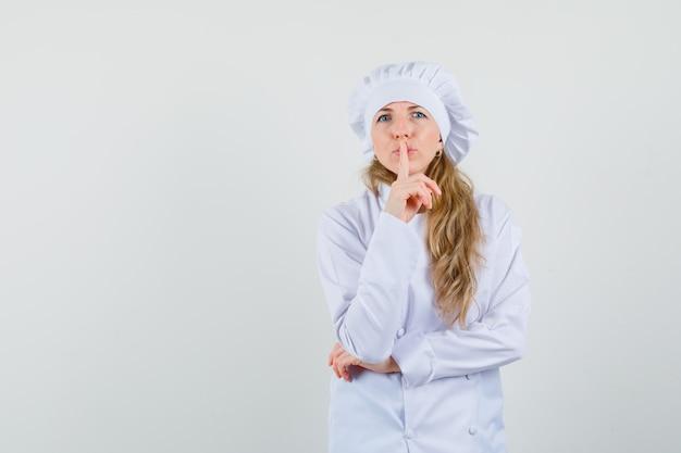 Köchin, die stille geste in der weißen uniform zeigt und vorsichtig schaut.