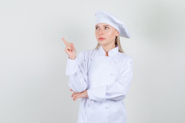 Köchin, die weg zeigt und in weißer uniform zur seite schaut