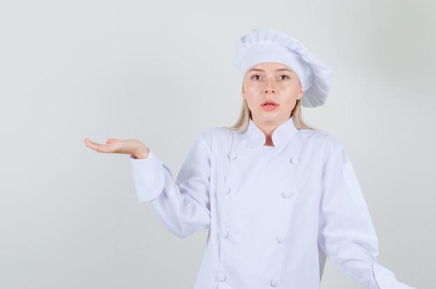 Köchin gestikuliert, als würde sie etwas in weißer uniform halten und verwirrt aussehen