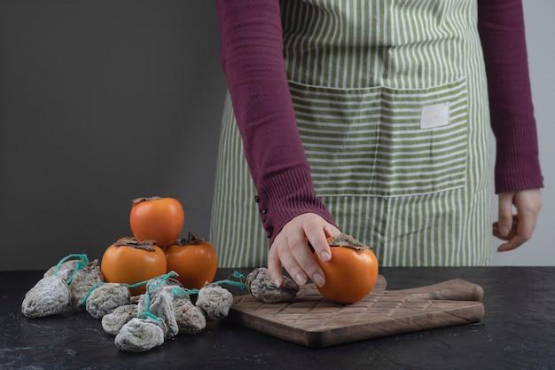 Köchin hält einzelne kaki-frucht auf schwarzem tisch