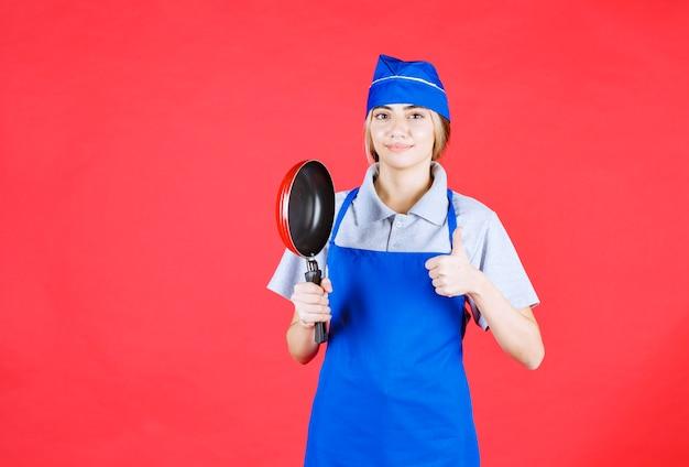 Köchin in blauer schürze, die eine tefal-pfanne hält und zufriedenheitszeichen zeigt
