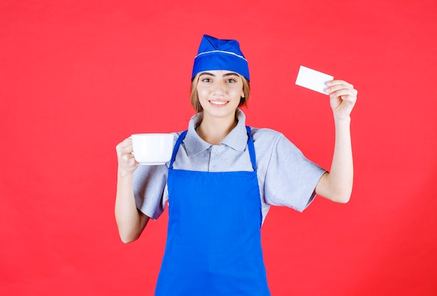 Köchin in blauer schürze, die eine weiße nudeltasse aus keramik hält und ihre visitenkarte präsentiert