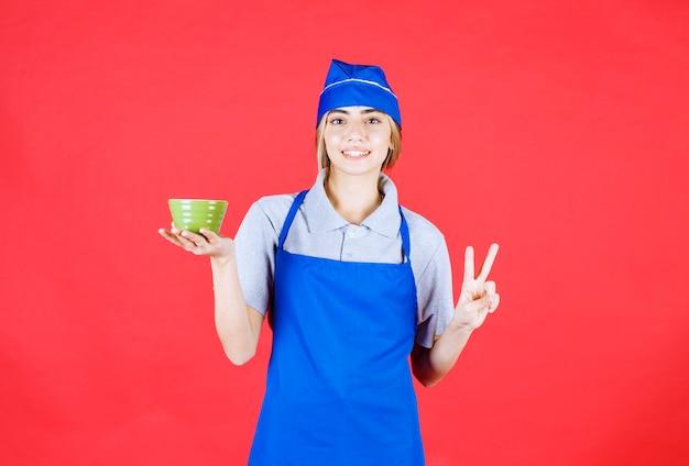 Köchin in blauer schürze, die einen nudelbecher hält und zufriedenheitshandzeichen zeigt