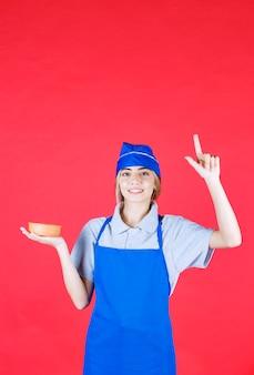 Köchin in blauer schürze hält eine nudeltasse und sieht verwirrt aus und denkt darüber nach, wie man es leckerer machen kann