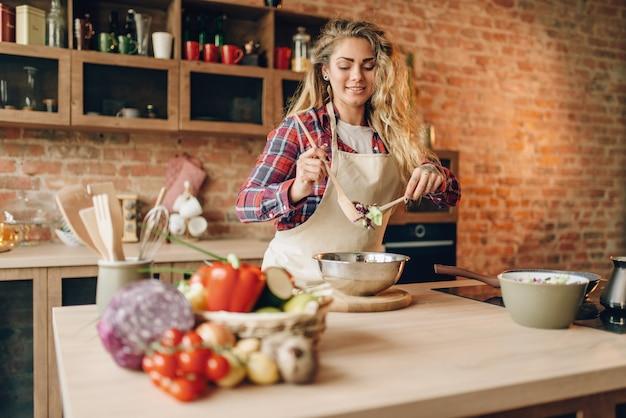 Köchin in der schürze bereitet frischen salat zu