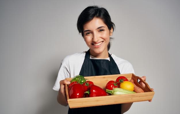 Köchin in der schwarzen schürze, die gemüse schneidet, kocht lebensmittel gesundes lebensmittelhaushalt