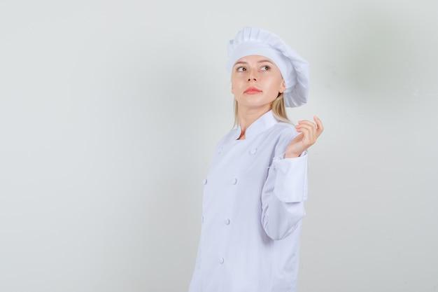 Köchin in der weißen uniform, die beim schauen beiseite wirft