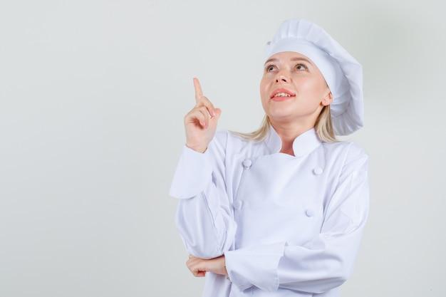 Köchin in der weißen uniform, die finger zeigt und fröhlich schaut