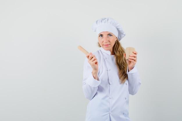 Köchin in der weißen uniform, die mörser und stößel hält und fröhlich schaut