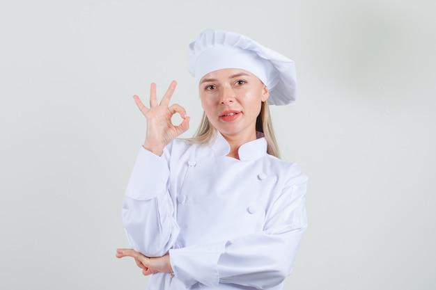 Köchin in der weißen uniform, die ok zeichen zeigt und positiv schaut