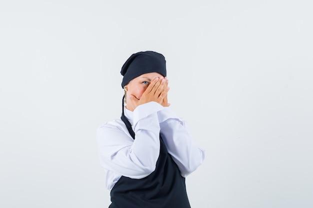 Köchin in uniform, schürze, die durch hände schaut und neugierig schaut, vorderansicht.