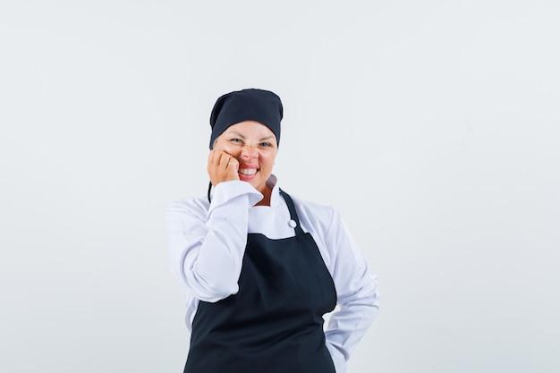 Köchin in uniform, schürze, die hand auf wange hält und niedlich, vorderansicht schaut.