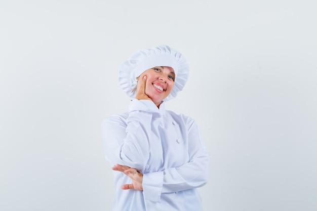 Köchin in weißer uniform, die das kinn auf der hand stützt und fröhlich aussieht