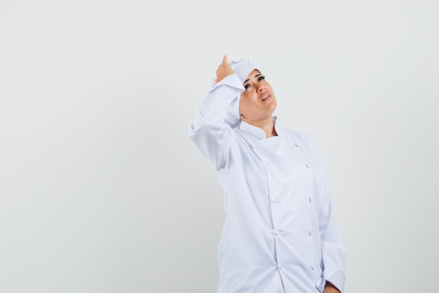 Köchin in weißer uniform, die hand auf kopf hält und traurig aussieht