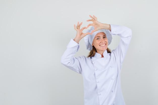 Köchin in weißer uniform, die herzform macht und glücklich schaut