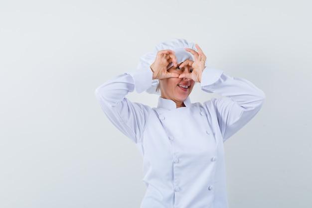 Köchin in weißer uniform, die herzgeste zeigt und froh aussieht