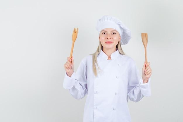 Köchin in weißer uniform, die holzgabel und -spatel hält und fröhlich schaut