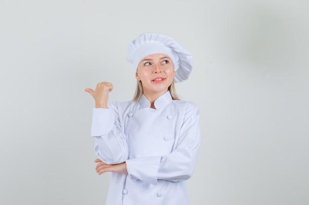 Köchin in weißer uniform, die mit daumen zurück zeigt und lächelt