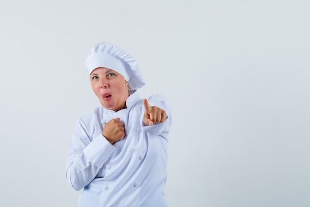 Köchin in weißer uniform, die mit einer hand auf der brust nach vorne zeigt und erstaunt aussieht