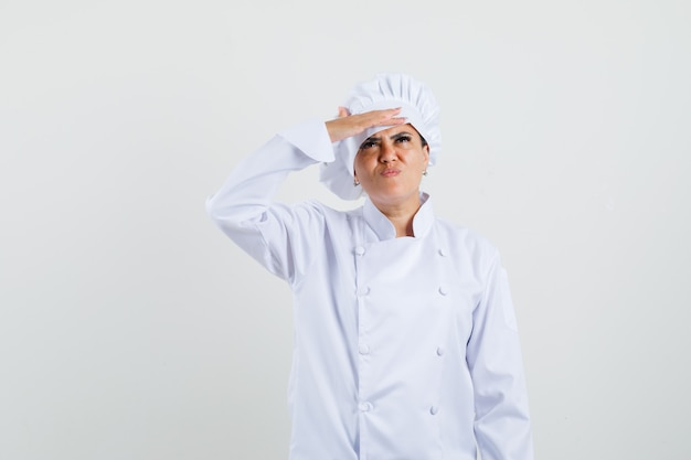 Köchin in weißer uniform, die mit hand über augen nach oben schaut