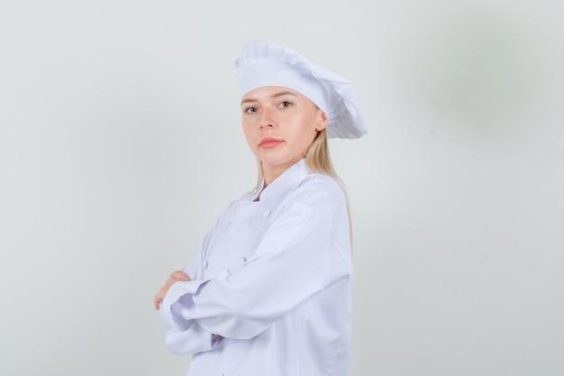 Köchin in weißer uniform, die mit verschränkten armen steht und selbstbewusst aussieht