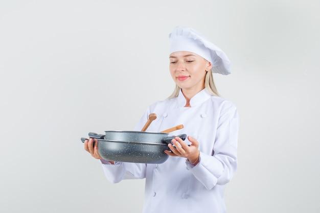 Köchin in weißer uniform, die pfannen mit hölzernen utensilien hält und fröhlich schaut