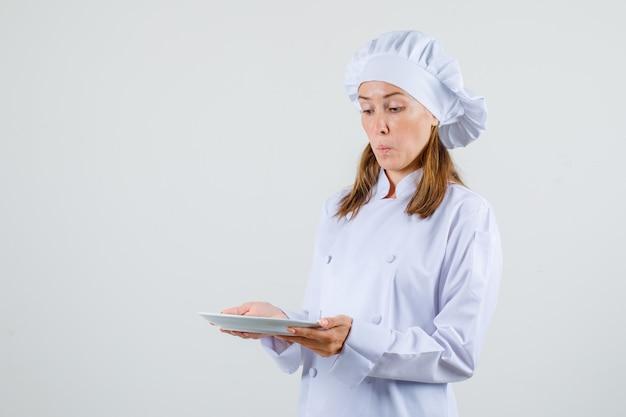 Köchin in weißer uniform, die platte hält und aufgeregt schaut