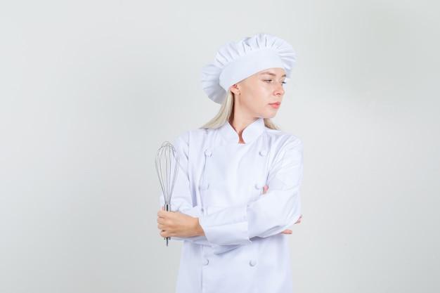 Köchin in weißer uniform, die schneebesen hält und beiseite schaut