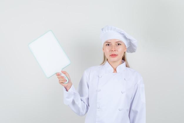 Köchin in weißer uniform, die schneidebrett hält und lächelt