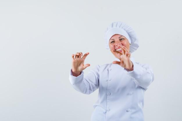 Köchin in weißer uniform posiert wie ein foto von jemandem und sieht zufrieden aus