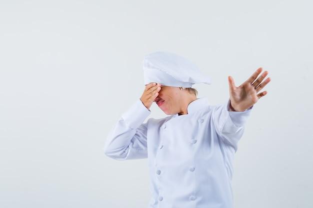 Köchin in weißer uniform posiert wie telefon zeigen und unzufrieden aussehen