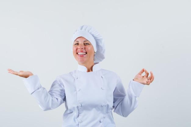 Köchin in weißer uniform zeigt eine gute geste, während sie die offene handfläche beiseite spreizt und optimistisch aussieht
