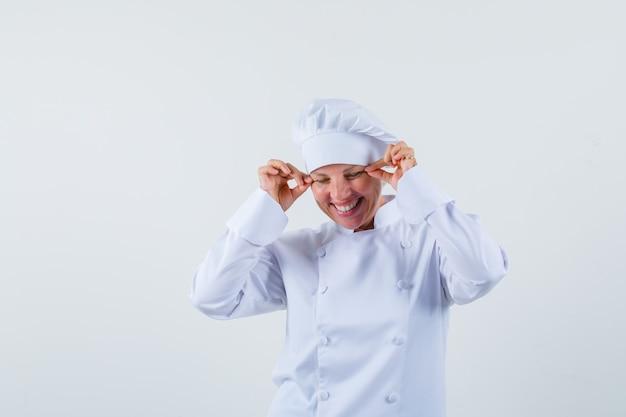 Köchin kneift ihre augenlider in weißer uniform und sieht verrückt aus.