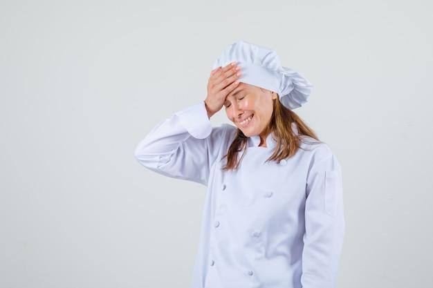Köchin lächelnd mit hand auf stirn in weißer uniform