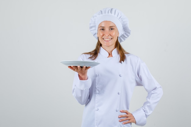 Köchin lächelnd und teller in weißer uniform haltend