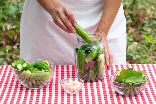 Köchin legt frische gurke zur konservierung in ein glas