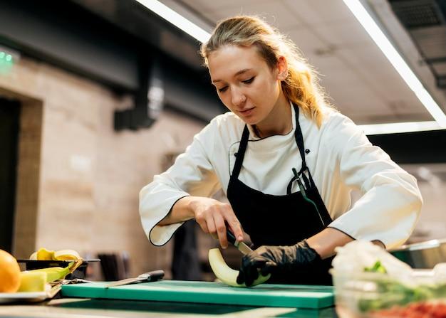 Köchin mit handschuh, die banane schneidet