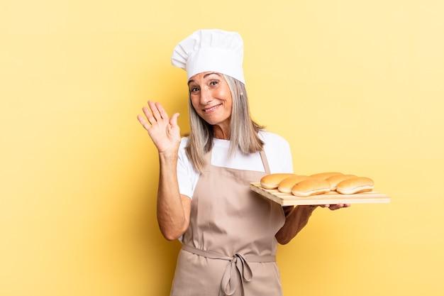 Köchin mittleren alters, die glücklich und fröhlich lächelt, mit der hand winkt, sie begrüßt und begrüßt oder sich verabschiedet und ein brottablett hält