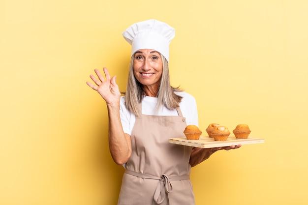 Köchin mittleren alters, die glücklich und fröhlich lächelt, mit der hand winkt, sie begrüßt und begrüßt oder sich verabschiedet und ein muffins-tablett hält