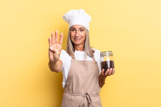 Köchin mittleren alters, die lächelt und freundlich aussieht, die nummer vier oder vier mit der hand nach vorne zeigt, herunterzählen und kaffeebohnen halten