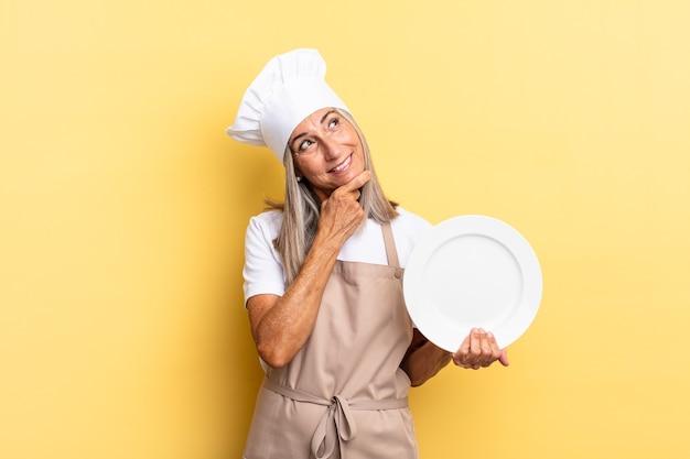 Köchin mittleren alters, die mit einem glücklichen, selbstbewussten ausdruck mit der hand am kinn lächelt, sich wundert und zur seite schaut und ein gericht hält