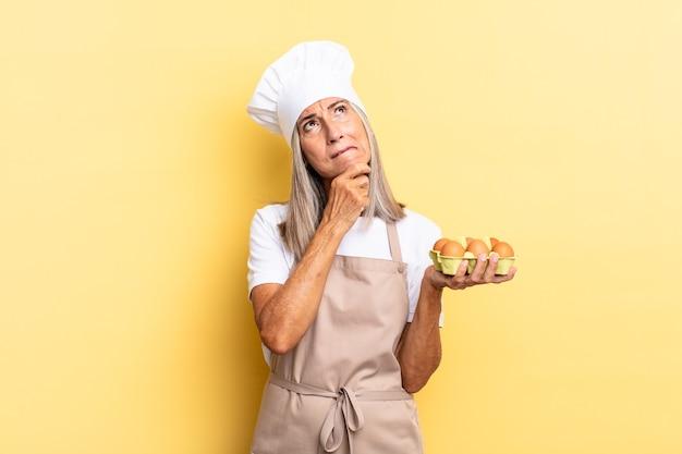Köchin mittleren alters, die nachdenkt, sich zweifelnd und verwirrt fühlt, mit verschiedenen optionen und sich fragt, welche entscheidung sie treffen soll, eine eierschachtel zu halten?