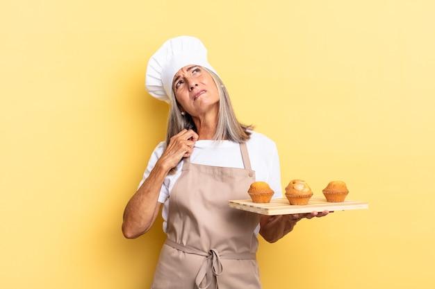 Köchin mittleren alters, die sich gestresst, ängstlich, müde und frustriert fühlt, am hemdkragen zieht, mit problemen frustriert aussieht und ein muffinsblech hält