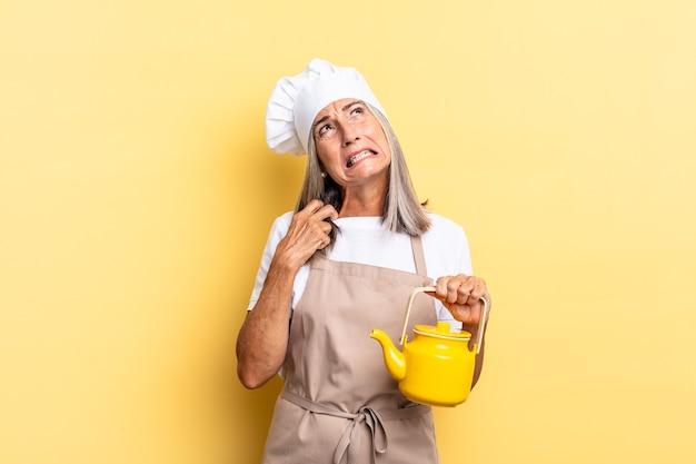 Köchin mittleren alters, die sich gestresst, ängstlich, müde und frustriert fühlt, den hemdkragen zieht, mit problemen frustriert aussieht und eine teekanne hält