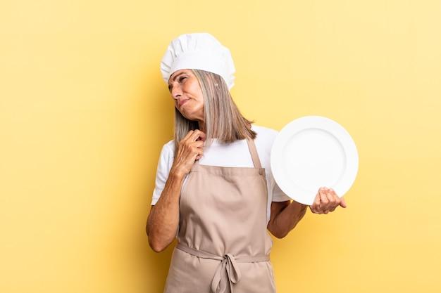 Köchin mittleren alters, die sich gestresst, ängstlich, müde und frustriert fühlt, hemdkragen zieht, mit problemen frustriert aussieht und ein gericht hält