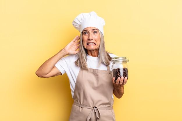 Köchin mittleren alters, die sich gestresst, besorgt, ängstlich oder ängstlich fühlt, mit den händen auf dem kopf, in panik geraten, wenn sie kaffeebohnen hält