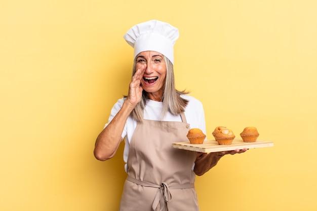 Köchin mittleren alters, die sich glücklich, aufgeregt und positiv fühlt, mit den händen neben dem mund einen großen schrei ausspricht, ein muffins-tablett ruft und hält